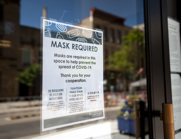 "A sign on a glass door says ""mask required"""