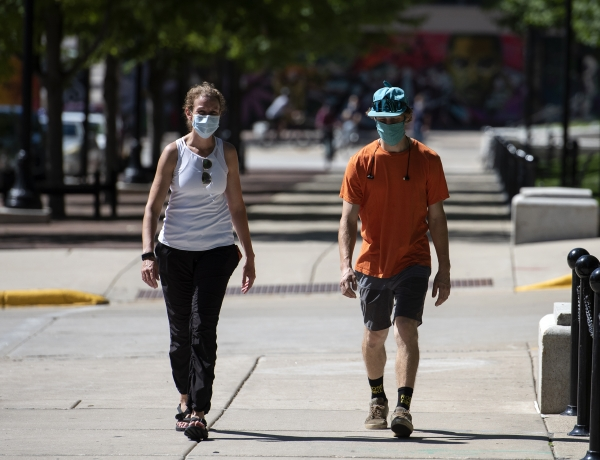 two people walk on a sidewalk near the capitol building in Downtown Madison while wearing masks