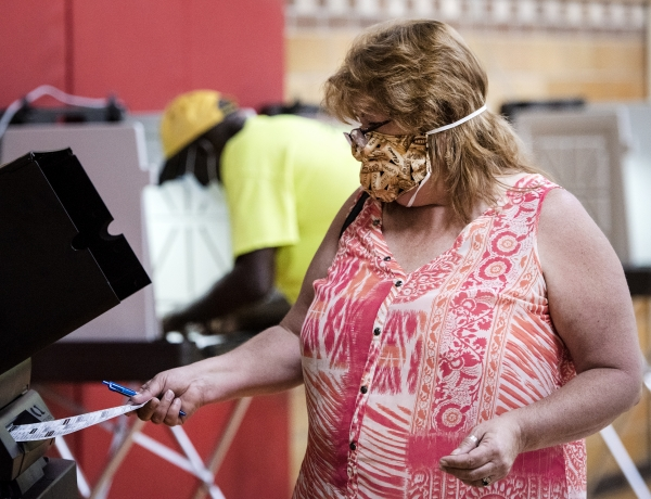 a woman in a mask places her ballot into the scanning machine