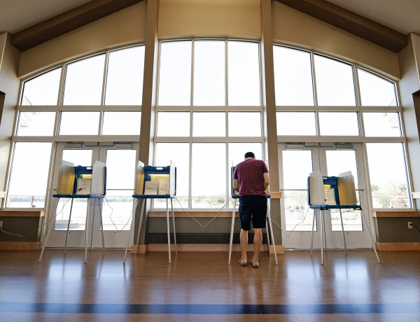 a voter is seen from behind as he votes at one of four available voting stations in front of a large window