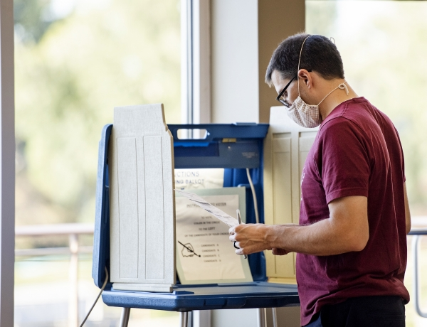 a man in a face mask holds a ballot