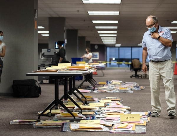 a man in a face mask walks by ballots placed on the floor and on a table