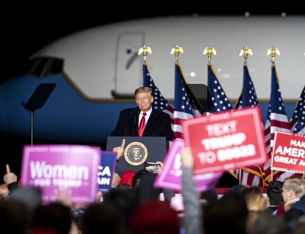 President Trump stands in front of Air Force One and a dark night sky as his supporters wave red and pink signs in the crowd