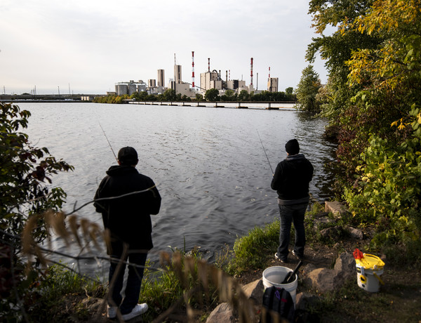 the paper mill can be seen across the water as two people fish from the grassy, unkempt shore
