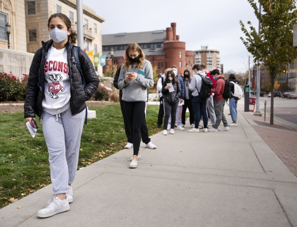 A student in a face mask and Bucky Badger t-shirt holds a ballot while waiting in line on a sidewalk