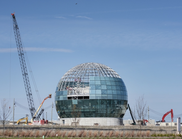 Cranes surround a large globe under a blue sky