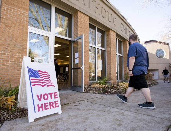 """a voter walks into a polling location. a sign says """"vote here."""""""