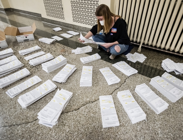 ballot envelopes surround a worker who sits on the floor