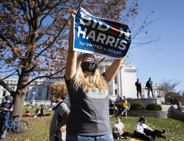 """A woman holds a """"Biden/Harris"""" sign in front of the state capitol"""
