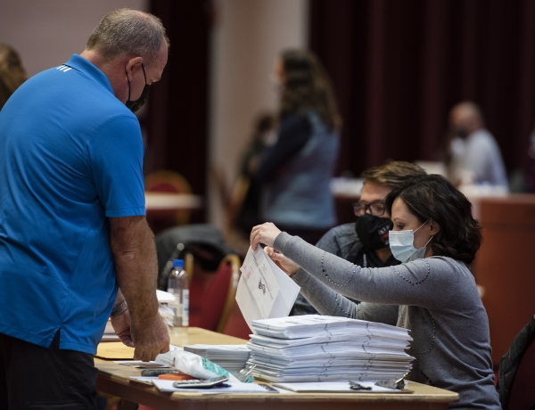Two workers go through a large stack of ballots on a table