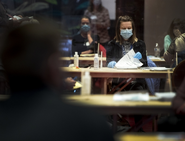Lines of tables can be seen as a worker in gloves and a face mask flips through ballots