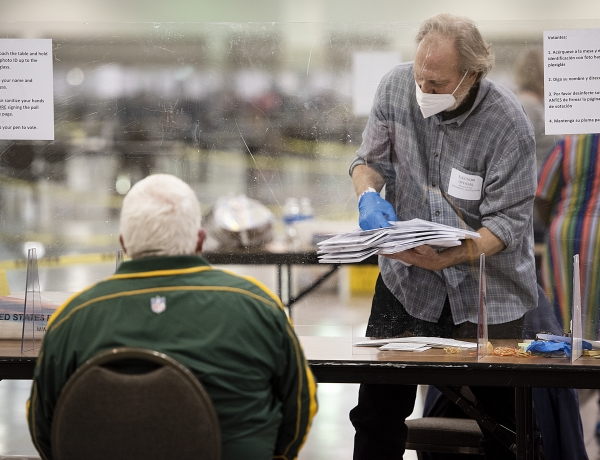 A man in gloves and a face mask carries a stack of ballots during the recount