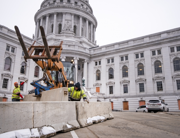 Two workers in yellow jackets stand in front of a construction vehicle as they place concrete barriers in front of the state capitol