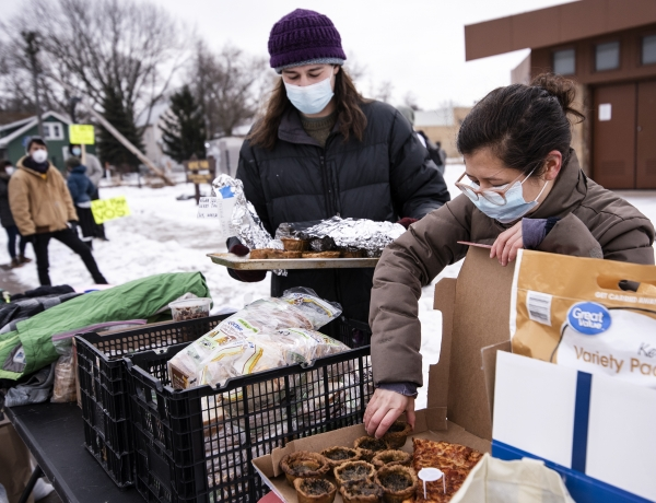 two people in winter gear and face masks place small tarts into a box next to other donated items