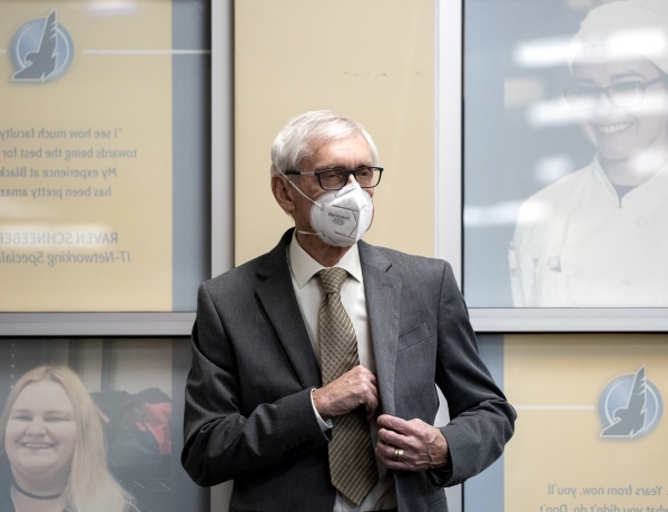 Gov. Tony Evers wears a white mask as he puts his notes in his jacket pocket