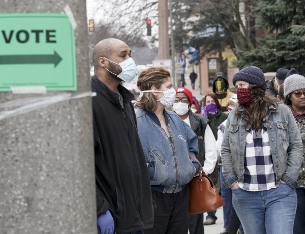 Voters masked against coronavirus line up at Riverside High School for Wisconsin's primary election Tuesday April 7, 2020, in Milwaukee