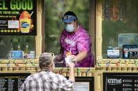 A woman in a mask hands a frozen treat to a customer from a food truck