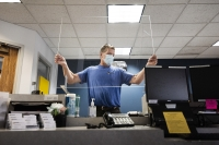 a man in a mask lifts a piece of plexiglass above a desk