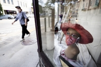 a mannequin bust is used to display a red cloth face mask in a window display as a pedestrian in a mask passes by