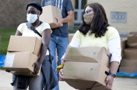 two volunteers carry two boxes of food each