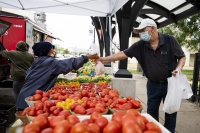 bright red tomatoes line a table as a customer in a face mask leans across to grab a bag from a woman
