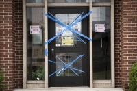 Blue painter's tape blocks off a doorway. several signs indicate that people should not enter.