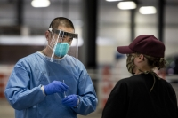 A man in a face shield, mask, blue gown, and gloves inserts a test swab into a container