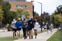 seven students run closely together on a sidewalk while wearing masks