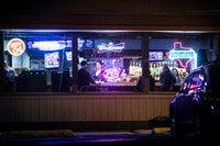 Neon signs illuminate the windows of a bar. a bar tender serving patrons can be seen inside.