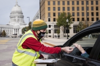 The Wisconsin State Capitol can be seen behind a poll worker in a mask and neon vest. He takes an ID card from a voter's hand as they sit in their car.