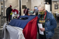 A voter in a Packers shirt and face mask uses an electronic machine to fill out a ballot