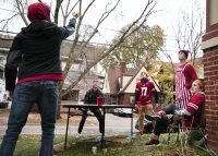 five students play a drinking game in a yard while wearing badgers gear