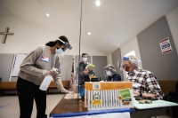 A woman in a mask and face shield holds a spray bottle and wipes a table with a cloth as poll workers sit across from her on the other side of plexiglass