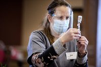 A pharmacist in gray scrubs and a face shield looks closely at a vial as she draws up a vaccine