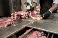 A worker wears black gloves as he slides a piece of meat into a band saw blade