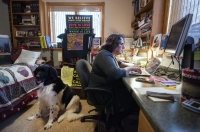 A large black and white dog sits on the ground behind Julie as she sits at her laptop.