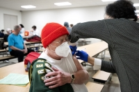 A man in a red hat and face mask closes his eyes as a vaccine is administered