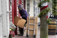 A Fed-Ex worker wearing a facemask makes a delivery