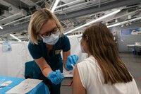 Jolanta Gawlik, left, gives Juliana Cepeda the Pfizer vaccine