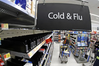 A woman looks at the few selections remaining in the cold and flu aisle