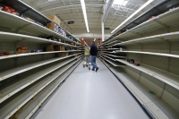 A man shops in an aisle of mostly empty shelves in a Walmart