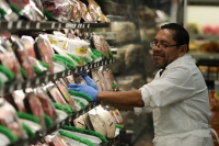 Jose Perez stocks meat wearing rubber gloves