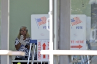 A polling place worker adjusts gloves as she tends to a reception table