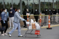 A man pushes a grocery cart while wearing a mask