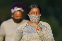Kedria Grigsby walks along a park trail while wearing a face mask to help prevent the spread of COVID-19