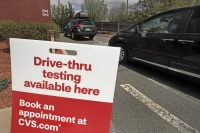 Cars idle in line as patients wait to self-take a COVID-19 virus test