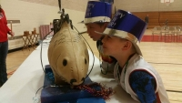 Two kids kiss Lucky the Carp at Carp Fest, a New Year's Eve celebration in Prairie du Chien