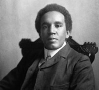 An old black and white photo of a Black man sitting in a chair, looking directly at the camera
