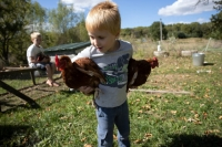 Matthias and Sterling Millar hold chickens outside their house