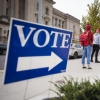 """A blue yard sign says """"VOTE"""" near a line of early voters"""